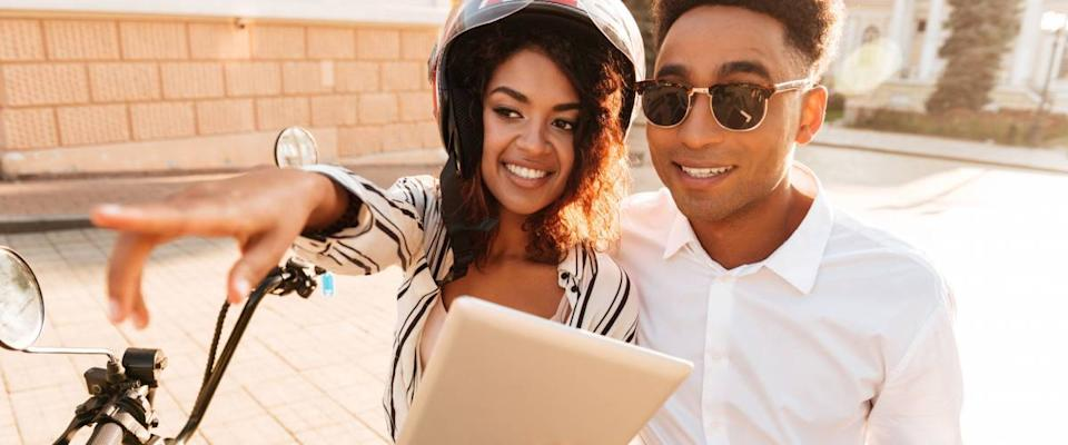 Close up picture of Happy african couple sitting on modern motorbike with tablet computer on the street while woman pointing away
