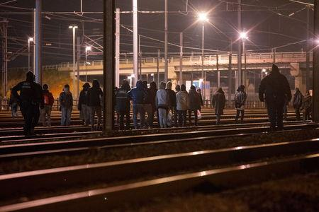 Police officers (L and R) push back migrants walking on the railway tracks of the freight shuttle leading to the entrance of the Channel Tunnel in Calais, France, October 14, 2015. REUTERS/Philippe Wojazer