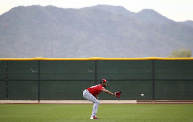 Cincinnati Reds pitcher Amir Garrett reaches out to make a catch as pitchers warm up during a workout at the Reds spring training baseball facility, Wednesday, Feb. 13, 2019, in Goodyear, Ariz. (AP Photo/Ross D. Franklin)