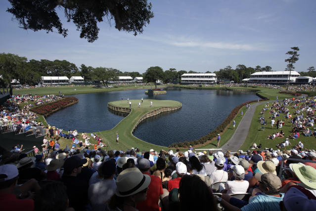FILE - In this May 9, 2014, file photo, golfers play the 17th hole during the second round of The Players Championship golf tournament at TPC Sawgrass in Ponte Vedra Beach, Fla. In a first for golf, The Players Championship will make available live streaming coverage of every shot from every player.(AP Photo/John Raoux, FIle)
