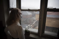 Bonney Ginett gazes out the window of her apartment in the Queens borough of New York on Thursday, March 18, 2021. Ginett, whose massage therapy business dried up during the pandemic, applied for help in July and said she was denied in October because she failed to prove loss of income. The 65-year-old New York City resident now owes more than $26,000 in back rent on her one-bedroom apartment and fears eviction. (AP Photo/Robert Bumsted)