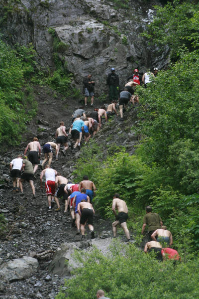 File - In this July 4, 2012 file photo, men's competitors in the annual Mount Marathon race in Seward, Alaska, struggle up the mountain. A rookie's disappearance during a popular extreme race on the mountain has led to new significant new rules in this year's event. Runners in the July Fourth race have to go halfway up Mount Marathon in an hour or they will have to turn around and participants also must sign a statement saying they've completed the entire race course all the way up the 3,022-foot peak. Organizers say the changes were prompted by the disappearance last year of 65-year-old Michael LeMaitre, who was slower than average in his first time on the mountain. (AP Photo/Mark Thiessen, File)