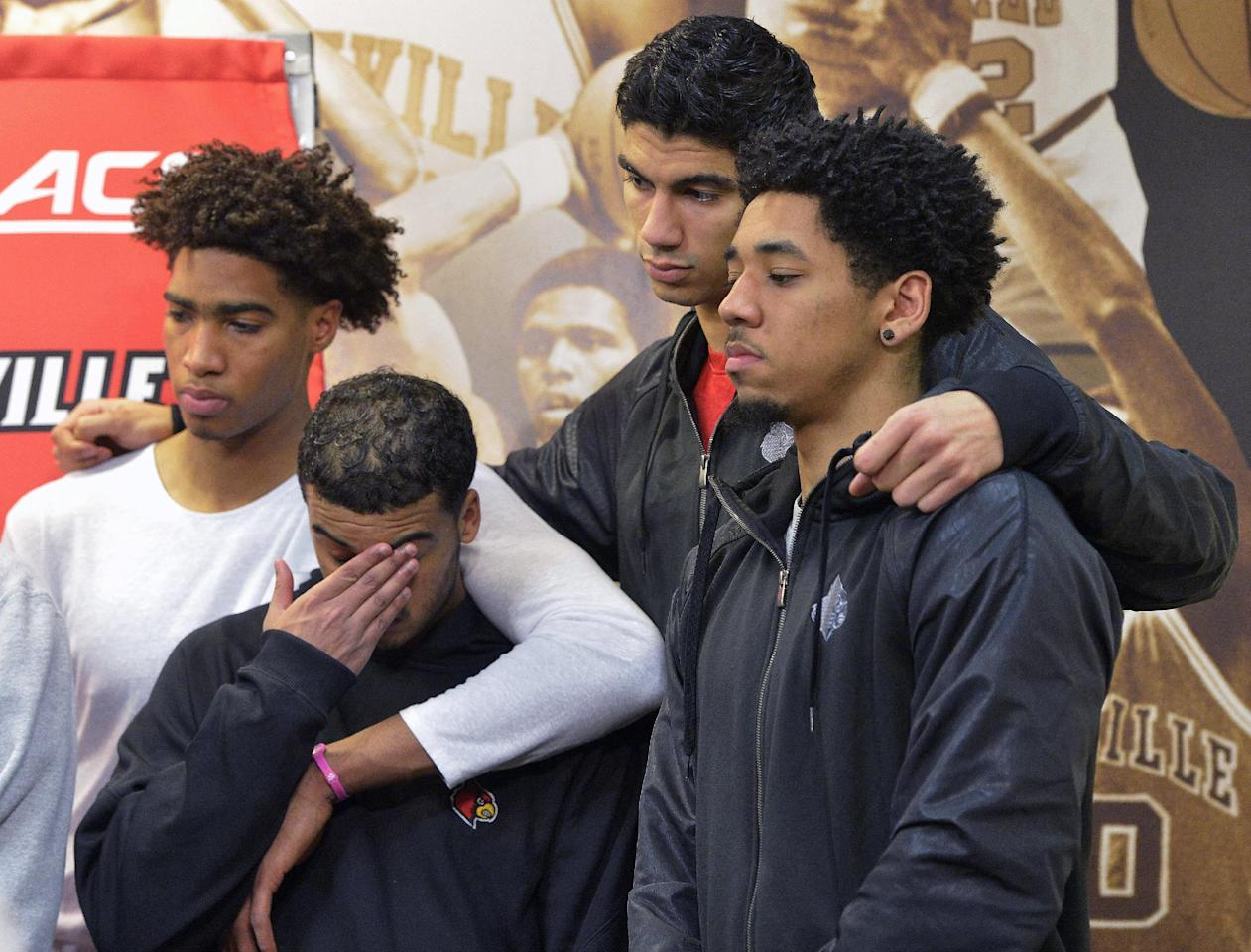 From left, Louisville players Ray Spalding, Quentin Snider, Anas Mahmoud, and Jay Henderson listen to teammates Damion Lee and Trey Lewis during a news conference Friday, Feb. 5, 2016, in Louisville Ky. The university president announced earlier in the day a one-year postseason ban for the Cardinals men's basketball team amid ongoing investigations into a sex scandal. (AP Photo/Timothy D. Easley)