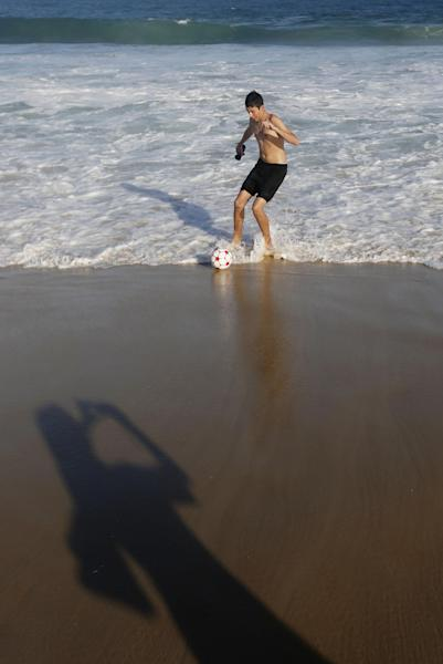 The shadow of a nun who takes pictures of a youth playing soccer is cast on Copacabana beach before a night vigil service with Pope Francis for World Youth Day in Rio de Janeiro, Brazil, Saturday, July 27, 2013. Pope Francis is speaking the language of Brazil's soccer-mad youth, telling them that being a good Catholic is like training to play soccer. (AP Photo/Jorge Saenz)