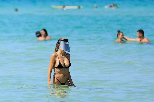 PHOTO: A woman wears a face shield as she wades in the ocean off South Beach in Miami Beach, Fla., on June 10, 2020. (Cliff Hawkins/Getty Images)
