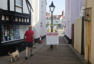 A man walks his dog past a sign requesting dog owners to pick-up the their pet's waste in Shaldon, Devon, England, Friday July 23, 2021. (AP Photo/Tony Hicks)