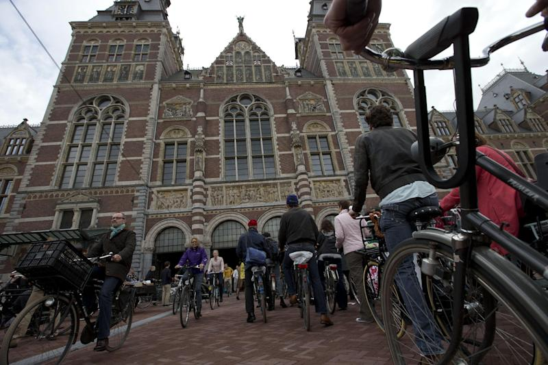 Hundreds of bicycles queue to pass  through Rijksmuseum, in Amsterdam, Netherlands, Monday May 13, 2013, signaling the end of more than a decade of efforts by cyclists to ensure a passageway that runs under and through the Rijksmuseum would remain open to bike traffic. The museum, which houses masterpieces by Rembrandt van Rijn and Vincent van Gogh, among others, opened last month after a 10-year renovation. Architects and successive museum directors had opposed allowing bikes through, and a local government tried to have them barred on safety grounds. But in a city that has more bicycles than people, the bike lobby prevailed. (AP Photo/Peter Dejong)