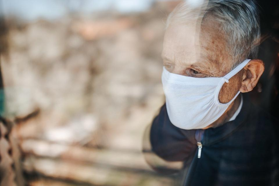 Senior man in home quarantine wearing a mask and looking through the window, during coronavirus COVID-19 epidemic.
