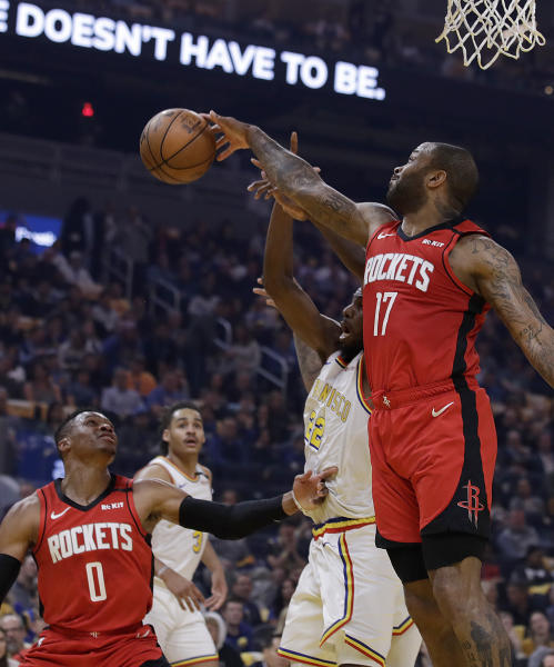 Houston Rockets' P.J. Tucker, right, rebounds over Golden State Warriors' Andrew Wiggins (22) in the first half of an NBA basketball game Thursday, Feb. 20, 2020, in San Francisco. (AP Photo/Ben Margot)