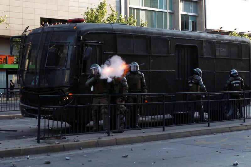 A riot police officer shoot a tear gas canister during a protest against the increase in the subway ticket prices in Santiago