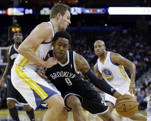 Golden State Warriors' David Lee, left, defends against Brooklyn Nets' MarShon Brooks (9) during the first half of an NBA basketball game in Oakland, Calif., Wednesday, Nov. 21, 2012. (AP Photo/Marcio Jose Sanchez)