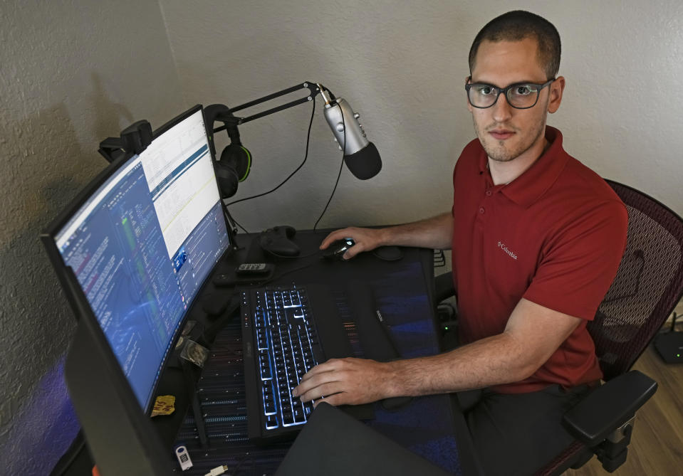 In this Sept. 20, 2021, photo Austin Moody poses for a photo as he sits a his home work station in Tampa, Fla. Moody, the Michigan native, got a scholarship from the Department of Defense that required working for the agency at least a year after graduating. Moody said he understands that state governments don't have the kind of money that federal agencies or private companies spend on recruiting and generous salaries. (AP Photo/Steve Nesius)