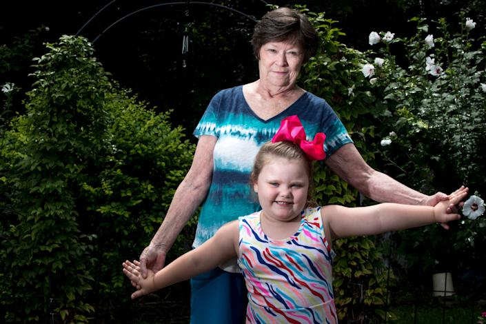 Mary Mahan, 71, stands with her granddaughter, Lyric, 4, who she is raising on Monday, Aug. 10, 2020, in Taylor Mill, Ky. Mahan is at high risk for COVID-19 because of both her age and having suffered from breast cancer twice. Due to her risk she has opted to keep Lyric home from preschool for online schooling.