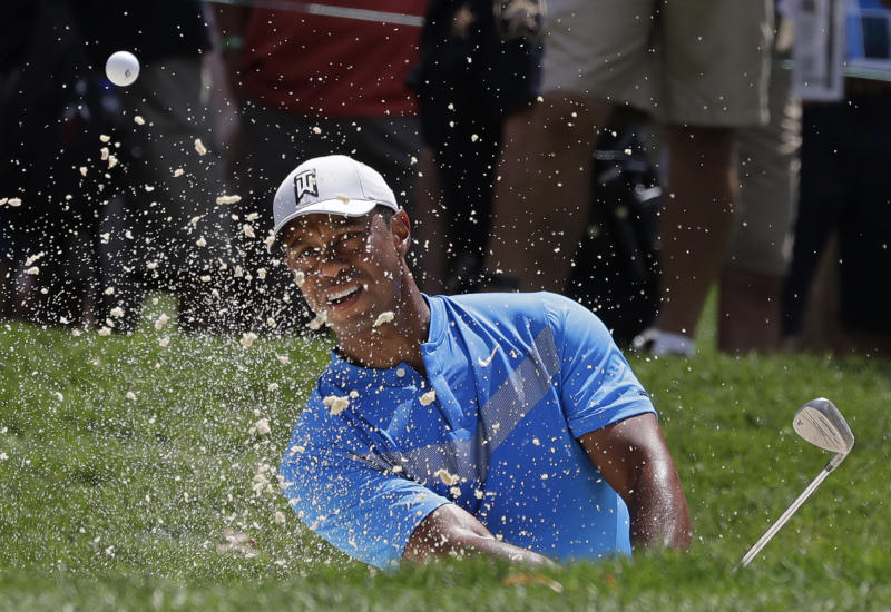 Tiger Woods hits from a sand trap on the fourth hole during the first round of the BMW Championship golf tournament at Medinah Country Club, Thursday, Aug. 15, 2019, in Medinah, Ill. (AP Photo/Nam Y. Huh)