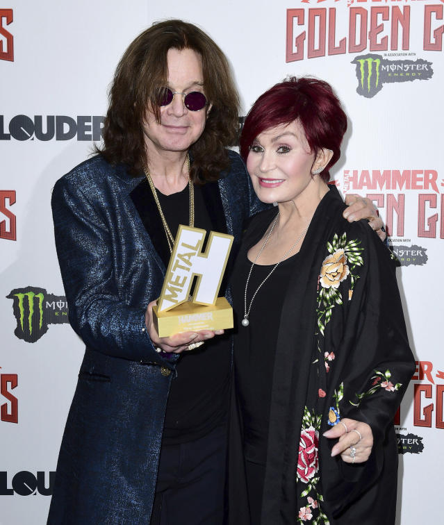Rock frontman Ozzy Osbourne holds his Golden God award, standing with his wife Sharon Osbourne in the press room during the Metal Hammer Golden Gods Awards 2018 ceremony in London, Monday June 11, 2018. (Ian West/PA via AP)