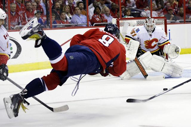 Washington Capitals right wing Alex Ovechkin (8), from Russia, makes a diving shot that is blocked by Calgary Flames goalie Karri Ramo (31), from Finland, in the first period of an NHL hockey game on Thursday, Oct. 3, 2013, in Washington. (AP Photo/Alex Brandon)
