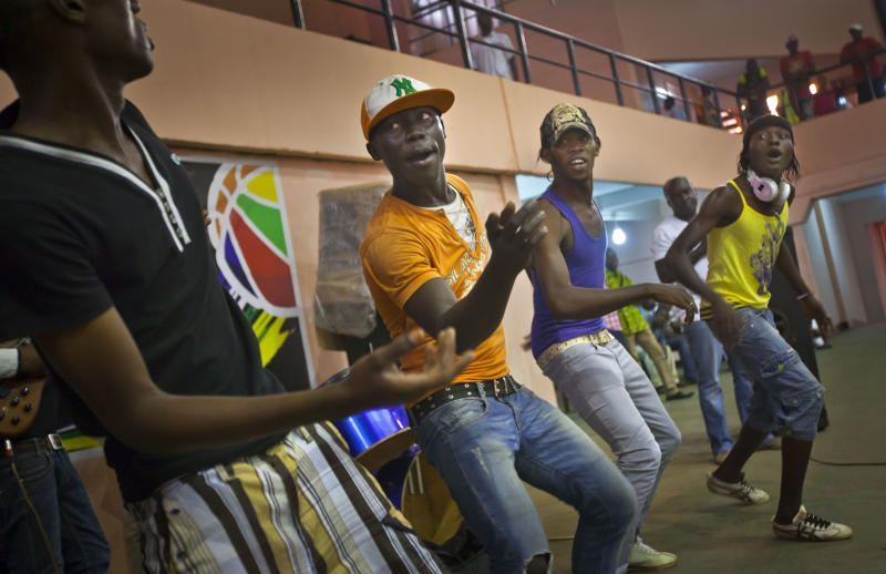 """Youths dance in the rap band entertaining a meeting of the National Youth Council to discuss the current crisis and the message that youth want to send to upcoming peace talks in Libreville, at the basketball stadium in the capital Bangui, Central African Republic Friday, Jan. 4, 2013. The U.N. children's agency UNICEF says it is concerned about a growing number of children being recruited by armed groups in Central African Republic as President Francois Bozize's government faces a rebellion in the north, saying Friday that it has received """"credible reports that rebel groups and pro-government militias are increasingly recruiting and involving children in armed conflict"""". (AP Photo/Ben Curtis)"""