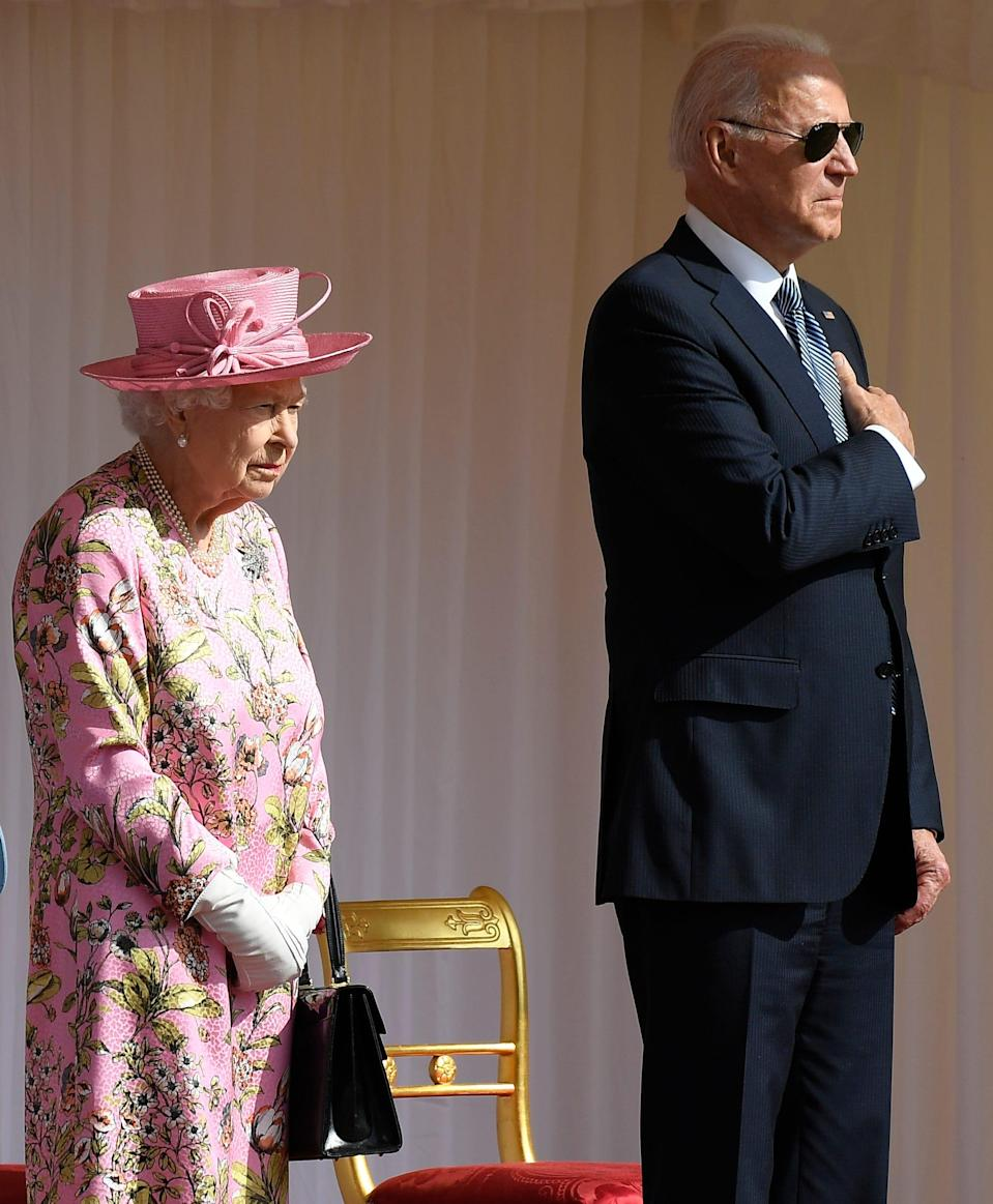 Britain's Queen Elizabeth II stands with US President Joe Biden as they listen to the US national anthem at Windsor Castle near London, Sunday, June 13, 2021. (AP Photo/Alberto Pezzali) ORG XMIT: TH130