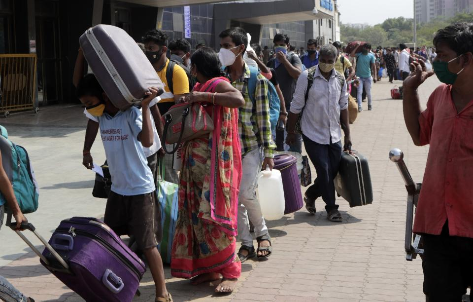 People wearing masks as a precaution against the coronavirus stand in a queue to board trains at Lokmanya Tilak Terminus in Mumbai, India, Friday, April 16, 2021. Migrant workers are swarming rail stations in India's financial capital Mumbai to go to their home villages as virus-control measures dry up work in the hard-hit region. The government of Maharashtra state imposed lockdown-like curbs on Wednesday for 15 days to check the spread of the virus. It closed most industries, businesses and public places and limited the movement of people, but didn't stop the bus, train and air services. An exodus ensued, with panicked day laborers hauling backpacks onto overcrowded trains leaving Mumbai, travel that raises fears of infections spreading in rural areas. (AP Photo/Rajanish Kakade)