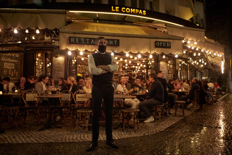 PARIS, FRANCE - SEPTEMBER 23: A waiter stands outside a busy terrace as Parisians relax as the French Government announced that from Monday all bars and cafes in Paris will be made to shut at 10pm as part of a string of new measures to curb the spread of Covid-19 in France on September 23, 2020 in Paris, France. With the rise in Coronavirus cases in France at 204 per 100,000 inhabitants, the French Government have followed other governments in introducing new restrictions aimed at reducing the spread of Covid-19 whilst avoiding another national lockdown. In large cities, including Paris, gatherings will be limited to ten people in public spaces, bars to close at 10 p.m., local and student parties will be prohibited. (Photo by Kiran Ridley/Getty Images)