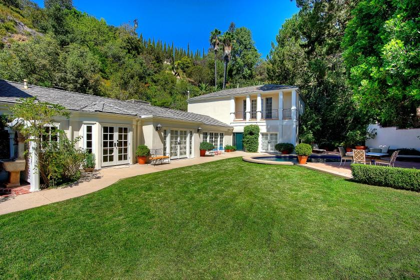 The secluded home in Hidden Valley expands to a landscaped yard and oval-shaped swimming pool.