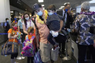 Hawaii residents Ryan Sidlow, center, carries his son Maxwell as their family boards a United Airlines flight to Hawaii at San Francisco International Airport in San Francisco, Thursday, Oct. 15, 2020. Coronavirus weary residents and struggling business owners in Hawaii will be watching closely as tourists begin to return to the islands on Thursday without having to self-quarantine upon arrival. (AP Photo/Jeff Chiu)