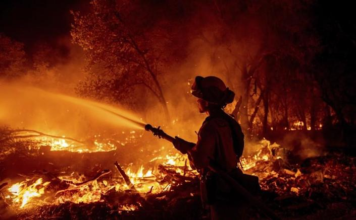Firefighter Ron Burias battles the Fawn Fire as it spreads north of Redding, Calif. in Shasta County, on Thursday, Sept. 23, 2021. (AP Photo/Ethan Swope)
