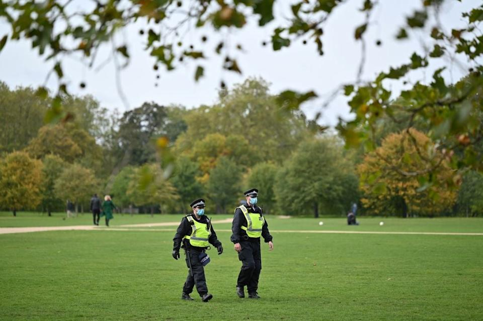 <p>Police wear face masks as they patrol a park</p> (AFP via Getty Images)