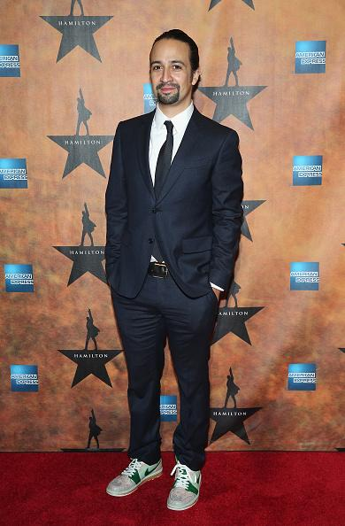 "<p>It's his night so he can wear sneakers if he wants to. Lin-Manuel Miranda, brains behind the smash hit musical ""Hamilton,"" wore a navy blue suit with high-top green and white sneakers. He also pulled his long hair back into a ponytail.</p>"