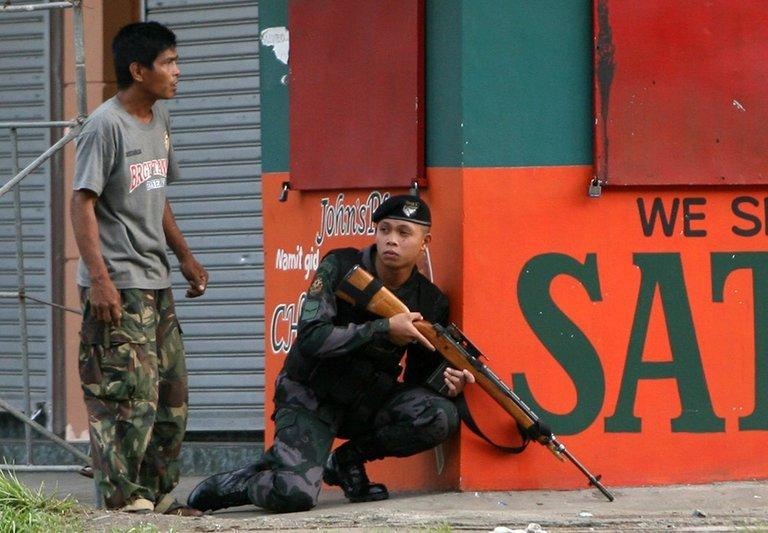A police sniper gets into position to confront MNLF rebels in Zamboanga City in the Philippines on September 9, 2013. A group of 100 rebels arrived by boat and took 20 civilians hostage, shooting dead a soldier and wounding six others