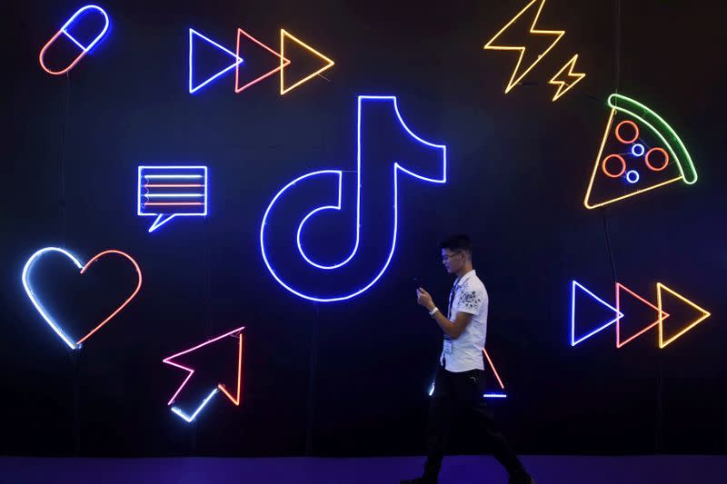 FILE PHOTO: Man walks past a sign of ByteDance's app TikTok, known locally as Douyin, at an expo in Hangzhou