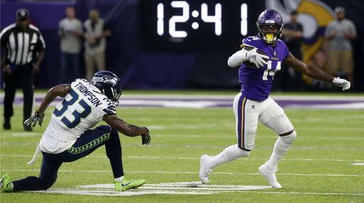 Minnesota Vikings wide receiver Stefon Diggs (14) runs from Seattle Seahawks defensive back Tedric Thompson (33) after making a reception during the first half of an NFL preseason football game, Friday, Aug. 24, 2018, in Minneapolis. (AP Photo/Jim Mone)