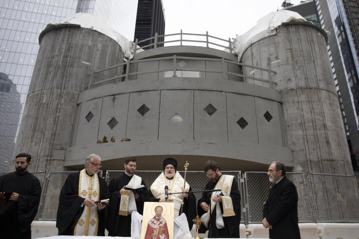 In this Dec. 6, 2019 photo, Greek Orthodox Archbishop Elpidophoros, center, leads clergy in a celebration of St. Nicholas Day in front of the St. Nicholas National Shrine at the World Trade Center in New York. Gov. Andrew Cuomo and officials with the Greek Orthodox church announced plans Thursday, Jan. 2, 2020, to resume construction with the goal of finishing the rebuilding on the church by the 20th anniversary of the terrorist attacks of Sept. 11, 2001. (AP Photo/Mark Lennihan)