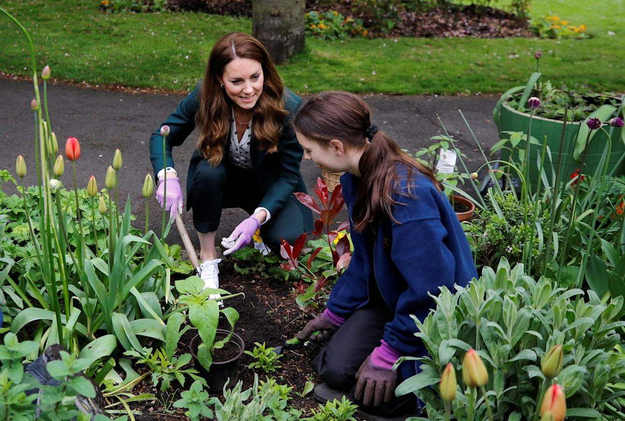EDINBURGH, SCOTLAND - MAY 27: Catherine, Duchess of Cambridge plants sunflower seeds with a volunteer during their visit to Starbank Park on May 26, 2021 in Edinburgh, Scotland. (Photo by Phil Noble - WPA Pool/Getty Images)