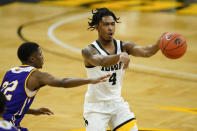 Iowa guard Ahron Ulis (4) passes ahead of Western Illinois guard Marcus Watson Jr., left, during the second half of an NCAA college basketball game, Thursday, Dec. 3, 2020, in Iowa City, Iowa. (AP Photo/Charlie Neibergall)
