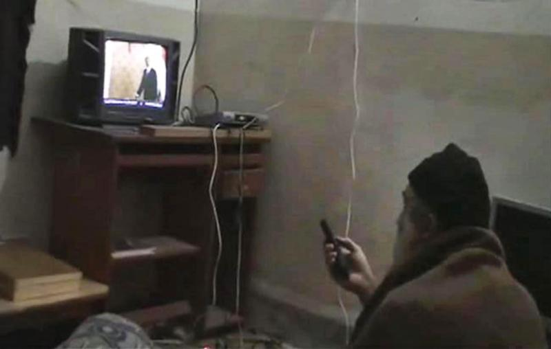 FILE - This undated image from video, seized from the walled compound of al-Qaida leader Osama bin Laden in Abbottabad, Pakistan, and released by the U.S. Department of Defense Saturday, May 7, 2011, shows a man, identified as Osama bin Laden, watching President Barack Obama on his television. A year after the U.S. raid on his compound bin Laden's al-Qaida terror network is hobbled and hunted, but still dreaming of payback. (AP Photo/Department of Defense, File)