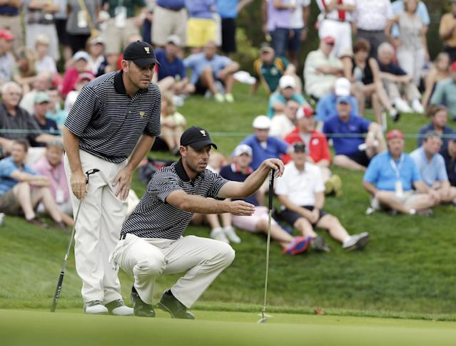 International team player Louis Oosthuizen, of South Africa,, left, and team player Charl Schwartzel discuss a putt on the fourth hole during a foursome match at the Presidents Cup golf tournament at Muirfield Village Golf Club, Friday, Oct. 4, 2013, in Dublin, Ohio. (AP Photo/Darron Cummings)