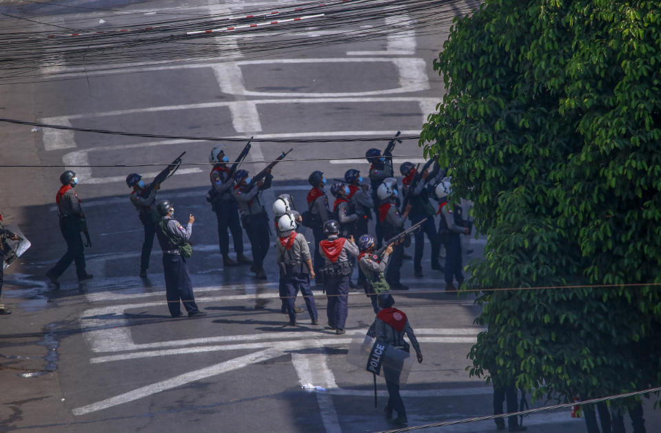 Police officers aim their guns towards people in nearby apartments as they stand off with anti-coup protesters in Yangon, Myanmar, Thursday, March 4, 2021. Demonstrators in Myanmar protesting last month's military coup returned to the streets Thursday, undaunted by the killing of at least 38 people the previous day by security forces. (AP Photo)