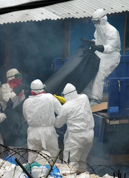 Medical workers wearing Personal Protection Equipment suits carry the body of a victim of the Ebola virus in a bag onto the back of a lorry at the John Fitzgerald Kennedy hospital in Monrovia, on September 5, 2014 (AFP Photo/Dominique Faget )