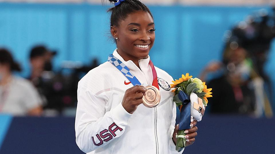 Simone Biles, pictured here with her bronze medal after the balance beam final.