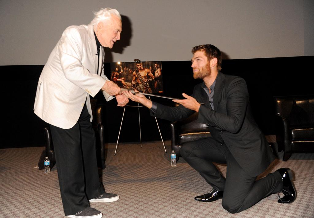 "Starz lead actor, Liam McIntyre, who portrays Spartacus, knelt to present legend Kirk Douglas with a special sword actually from the TV series, with a custom inscription: ""For Kirk, the original hero. Stand together or fall divided."""