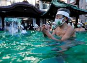Participants wearing protective face masks amid the coronavirus disease (COVID-19) outbreak, take an ice-cold bath at a ceremony in Tokyo