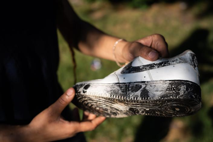 Anna Robinson holds up her Nike sneaker customized with skeletal art by her stepbrother, Derrick Magee. Derrick started a side business stenciling sneakers during the pandemic, in hopes of helping his family financially.