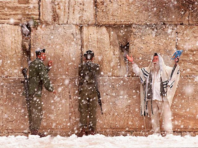 <p>An ultra-Orthodox Jew raises his arms as he recites a prayer while two Israeli soldiers also offer prayers during heavy snowfall at the Western Wall in the Old City of Jerusalem, March 18, 1998. (Photo: Jacqueline Larma/AP) </p>