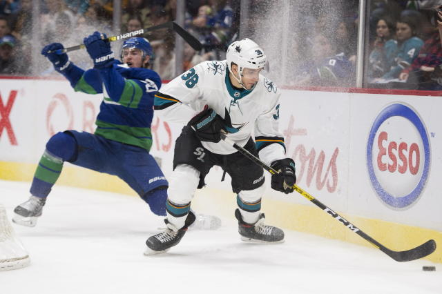 Vancouver Canucks left wing Tanner Pearson (70) fights for control of the puck with San Jose Sharks defenseman Mario Ferraro (38) during the third period of an NHL hockey game Saturday, Jan. 18, 2020, in Vancouver, British Columbia. (Jonathan Hayward/The Canadian Press via AP)