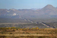 The newly erected border wall, that separates the United states and Mexico, right, leads towards the dynamited mountaintop path, Tuesday, Dec. 8, 2020, as seen from Douglas, Ariz. Construction of the border wall, mostly in government owned wildlife refuges and Indigenous territory, has led to environmental damage and the scarring of unique desert and mountain landscapes that conservationists fear could be irreversible. (AP Photo/Matt York)