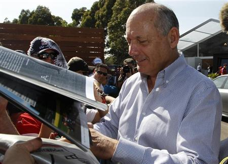 Chairman and CEO of McLaren Formula One team Dennis signs autographs at the first practice session of the Australian F1 Grand Prix in Melbourne