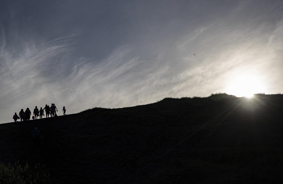 People walk on a dune, a day before a total eclipse in Nahuelpan, La Araucania, Chile, Sunday, Dec. 13, 2020. The total eclipse will be visible from Chile and the northern Patagonia region of Argentina, and as a partial solar eclipse in Bolivia, Brazil, Ecuador, Paraguay, Peru and Uruguay. (AP Photo/Esteban Felix)