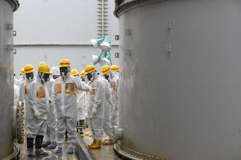 In this photo provided by Nuclear Regulation Authority (NRA), NRA commissioners inspect storage tanks used to contain radioactive water at the Fukushima Dai-ichi nuclear power plant, operated by Tokyo Electric Power Co. (TEPCO), in Okuma in Fukushima prefecture, northern Japan, Friday, Aug. 23, 2013. Deep beneath Fukushima's crippled nuclear power station a massive underground reservoir of contaminated water that began spilling from the plant's reactors after the 2011 earthquake and tsunami has been creeping slowly toward the sea. Now, 2 1/2 years later, experts fear it is about to reach the Pacific and greatly worsen what is fast becoming a new crisis at Fukushima: the inability to contain vast quantities of radioactive water. (AP Photo/Nuclear Regulation Authority)
