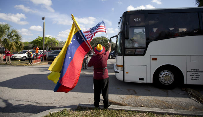 Xidmara Landaeta waves flags as Venezuelans from South Florida prepare for their bus trip to Washington, Thursday, May 8, 2014, in Doral, Fla. They are rallying to ask the Congress and President Barack Obama to impose economic sanctions and travel restrictions to the Venezuelan government officials because of presumed human right violations in the South American country. Organizers said they expect Venezuelans from 19 states will meet in Washington on Friday to demonstrate in front of the White House, Congress and the Organization of American States. (AP Photo/J Pat Carter)